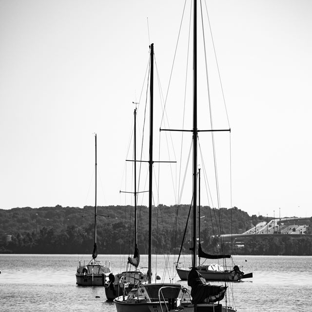 Black and white photo of three sailboats with sails down.